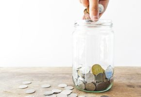 Woman putting coin in a jar for saving money