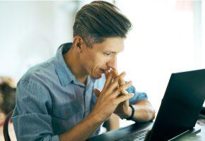 Emotional man looking at his laptop