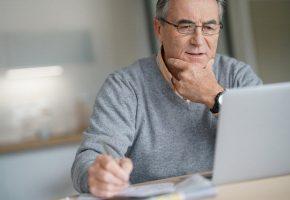 Senior man checking his laptop while writing